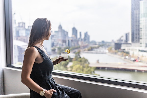 lady enjoying cocktail taking in city view from Crowne Plaza Melbourne