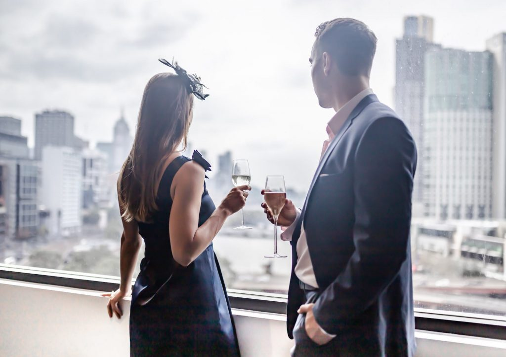 Man and woman holding wine glasses by the window