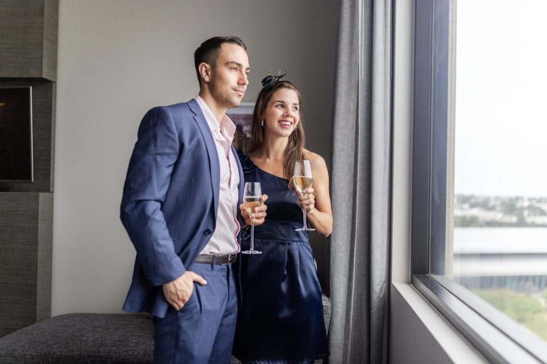 Couple standing near window with champagne at Crowne Plaza Melbourne