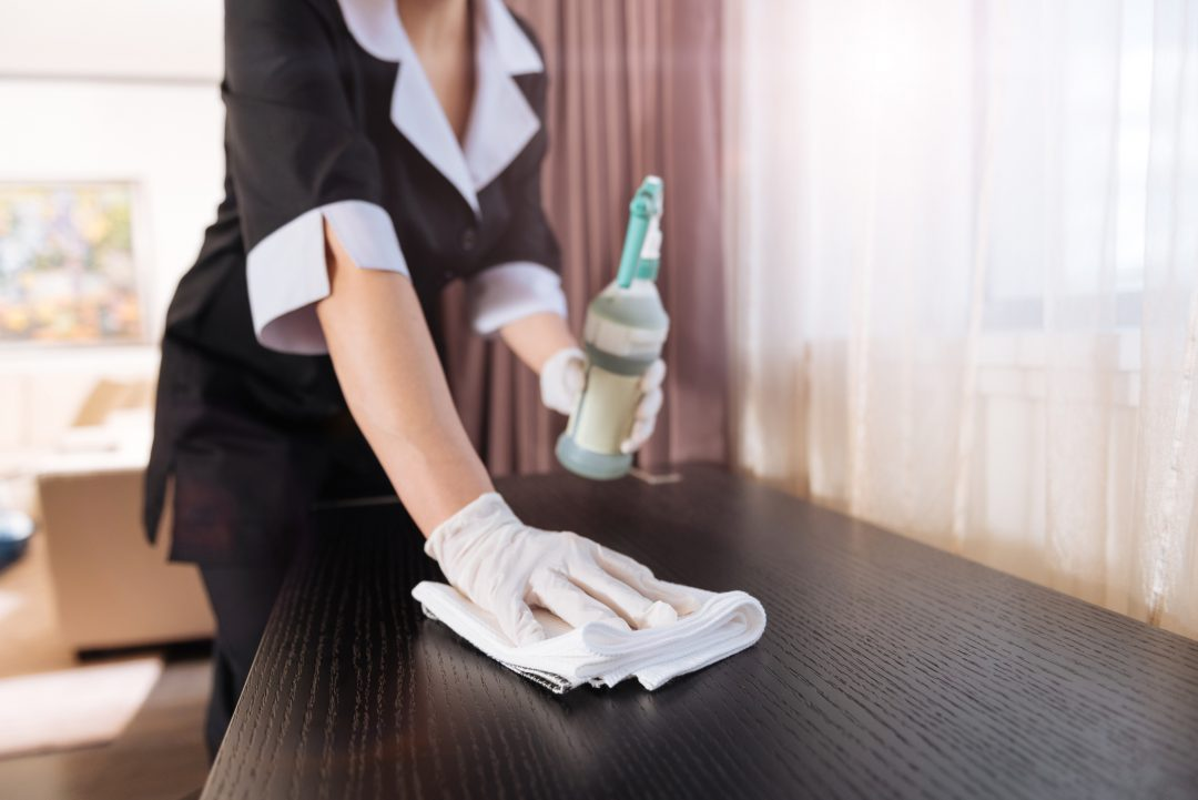 Perfect purity. Close up of a duster being used by a professional nice chambermaid while cleaning the table